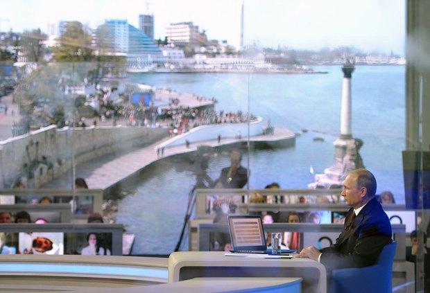 Путин в студии во время горяченй линии. Фон - фото набережной Севастополя