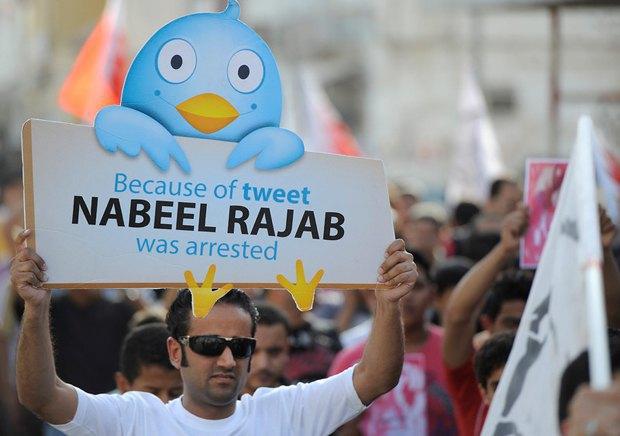 Активист держит плакат в поддержку арестованного правозащитника Набиля Раджаба за сообщения в Twitter