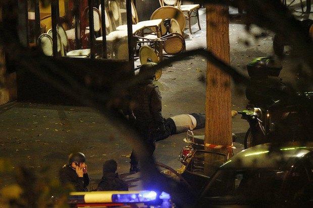 Полицейский стоит возле тела погибшего у концертного зала Батаклан