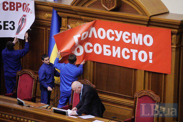 Работники Верховной Рады снимают плакаты с лозунгами оппозиции
