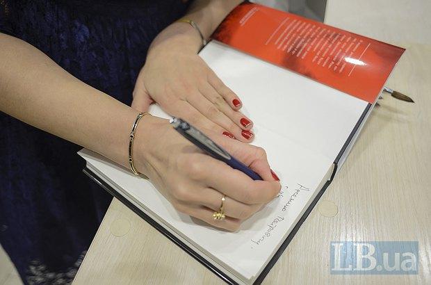 Соня Кошкина подписывает книгу для премьер-министра Украины Арсения Яценюка