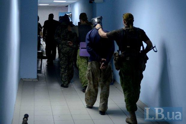 «Беркута» ведут боевиков, взятых в плен во время боя за воинскую часть неподалеку от поселка Металлист близ Луганска