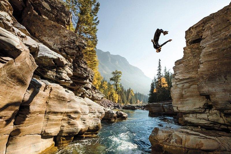 Стивен Донован прыгает со скалы в реку в Национальном парке Глейшер, куда он устроился на сезонную работу, Канада.
