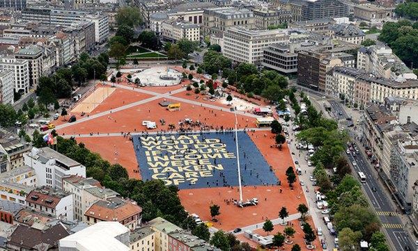 Гігантський плакат, розстелений в центрі Женеви напередодні референдуму з написом <<Що б ви зробили, якби ваш дохід був забезпечений?>>