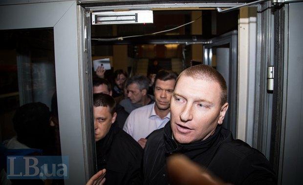 Олег Царев выходит из здания в сопровождении охраны