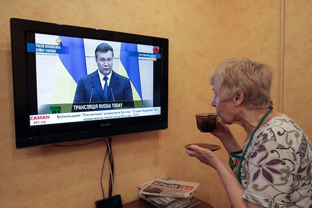 Жительница Симферополя смотрит трансляцию заявления Януковича по телевизору