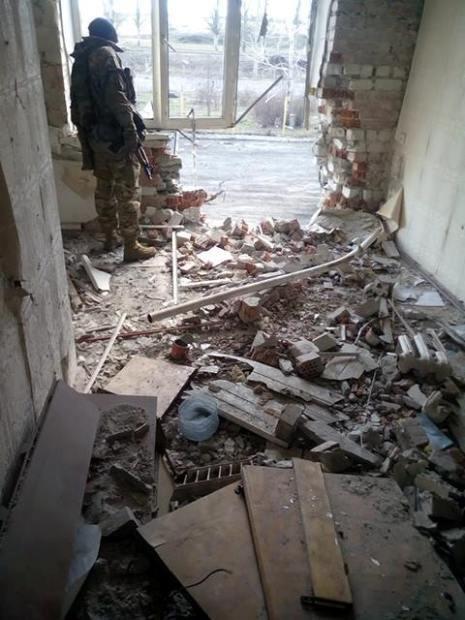 Боец 93-й ОМБр на позиции в полуразрушенном доме