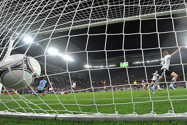 Игрок сборной Германии Ларс Бендер забивает победный гол в матче со сборной Дании