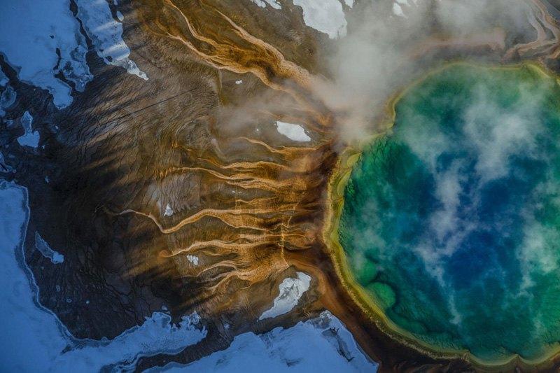Большой призматический источник - самый большой горячий источник США - отличается необычным цветом из-за термофильных бактерий, которые активно размножаются в кипящей воде.