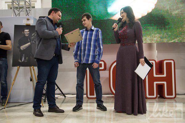Хирург Ростислав Валихновновский вручает сертификат на реконструктивную операцию в его клинике бойцу, который получил множественные осколочные ранения лица и тела