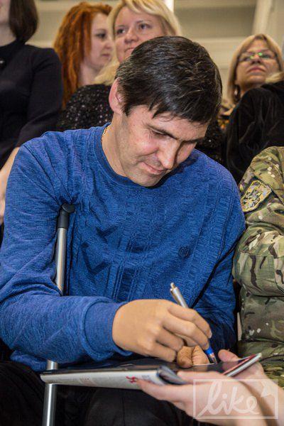 Слава Буйновский дает автограф протезированной рукой