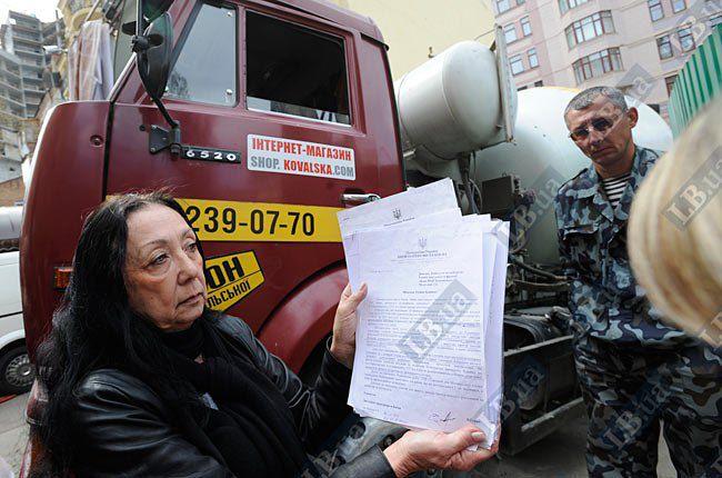 Местная жительница Лидия показывает документы о запрете строительства