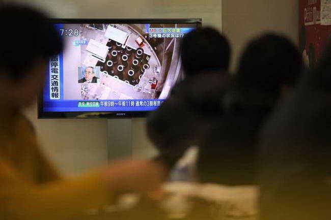Пассажиры в аэропорту смотрят телевизионные новости про взрыв на АЭС Фукусима-1