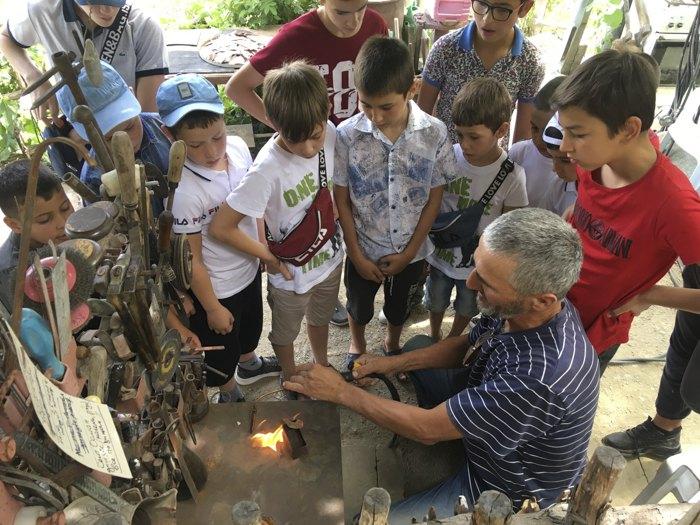 Майстер Рефат Куртвелієв навчає хлопчиків, як працювати з міддю та користуватися газовим пальником.
