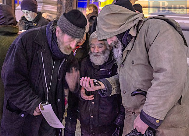 Бездомні дивляться телевізійний випуск за своєї участі на телефоні Юрія Ліфансе