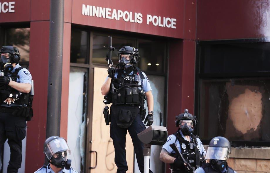 Полиция Миннеаполиса возле сожженного участка на второй день протестов в связи с смертью Джорджа Флойда, в Миннеаполисе, 27 мая 2020.