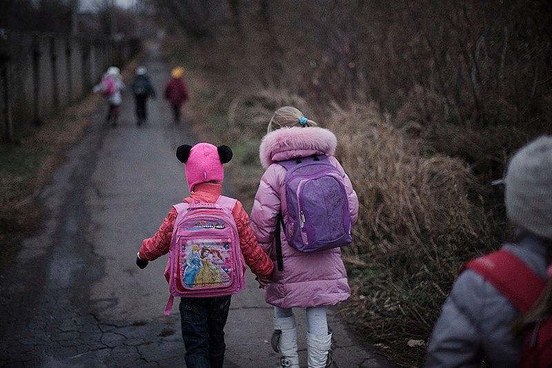 Аня з сестричками, доньки Ніни, під наглядом старшого хлопця-школяра, сусіда по вулиці, зі сміхом і писком біжить від зупинки шкільного автобуса до дому.