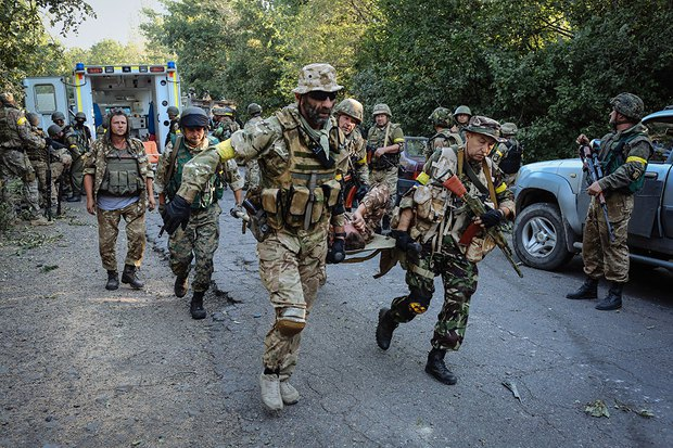 Николай Колесник(в центре) помогает нести раненого бойца под Иловайском. 10 августа 2014