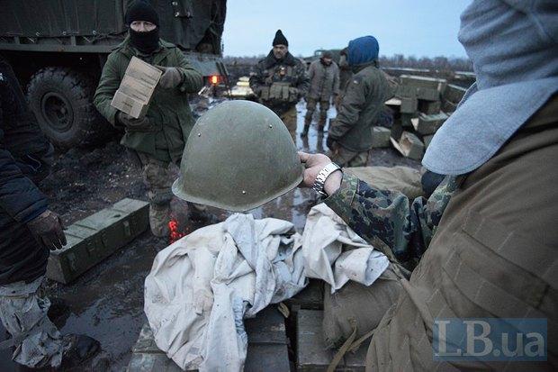 Артиллерист 44-ой бригады демонстрирует волонтерам каску, выданную МОУ, со слабой степенью защиты