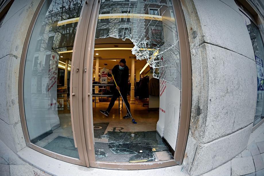 Працівник прибирає розбите скло в магазині вранці після нічних протестів у центрі Мадрида, 18 лютого 2021 р.