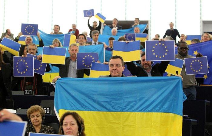 Депутати Європарламенту тримають прапори України та ЄС в знак підтримки акцій протесту в Києві під час сесії Європарламенту, Страсбург, 12 грудня 2013.