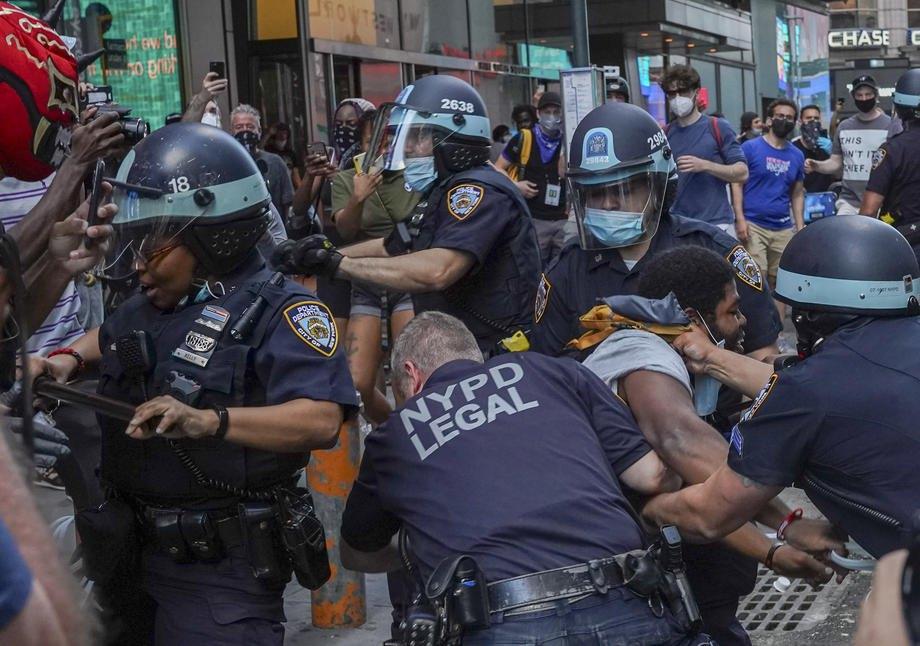 Сотрудники полиции Нью-Йорка оттесняют демонстрантов во время задержания на Таймс-сквер в Нью-Йорке, 30 мая 2020 .