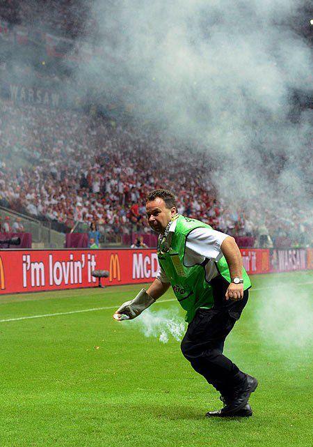 Працівник стадіону прибирає димову шашку, яку кинули на поле під час матчу Польща-Росія