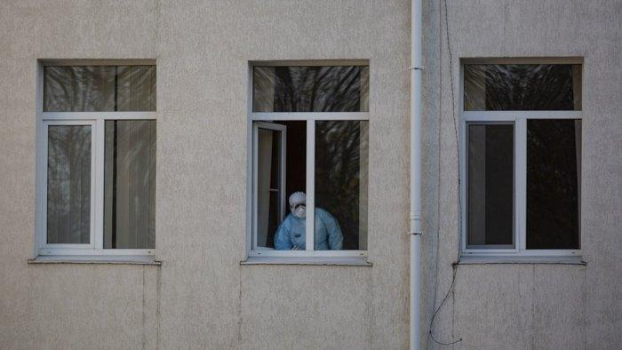 Медик у вікні Почаївськії обласної психоневрологічної лікарні, деу 26 пацієнтів було підтверджено COVID-19
