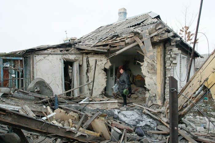 Женщина осматривает свой разрушенный дом после обстрелов в г. Ясиноватая, 21 декабря 2017.