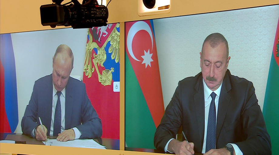 Президент Азербайджана Ильхам Алиев и президент России Владимир Путин подписывают документы во время видеоконференции, 9 ноября 2020 года.