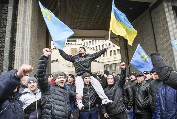 Активисты держат крымскотатарский и украинский национальные флаги во время митинга у здания крымского парламента в Симферополе, 26 февраля 2014.
