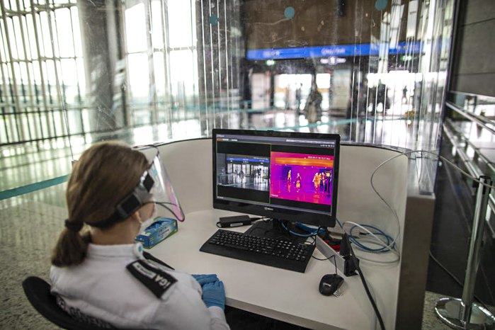 Офіцер безпеки дивиться на екран сканування температур пасажирів в аеропорту Стамбула, 01 червня 2020 року