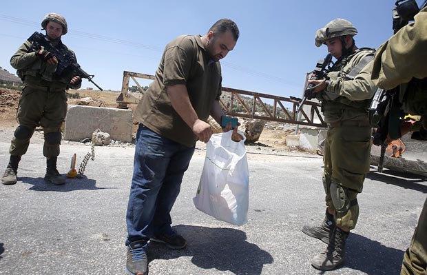 Израильские солдаты проверяют палестинца на КПП возле города Хеврон, 16 августа 2016 года.