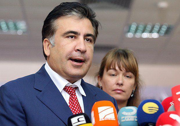 Президент Грузии Михаил Саакашвили отвечает на вопросы журналистов после того, как отдал свой голос на избирательном участке в Тбилиси, Грузия, 01 октября 2012 года (Сзади его жена Сандра Руловс)