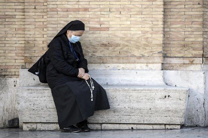 Монахиня молится во время всеобщей молитвы на площади Святого Петра в Ватикане.