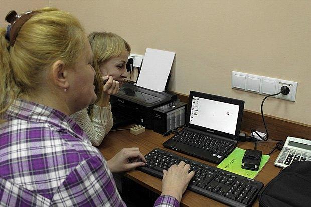 Оксана Потимко поряд зі своєю помічницею Мартою працює за ноутбуком
