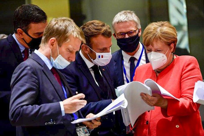 Канцлер Германии Ангела Меркель, президент Франции Эммануэль Макрон (в центре) и другие участники встречи на четвертый день саммита в Брюсселе, 20 июля 2020.