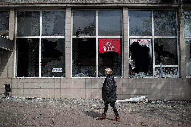 Женщина проходит мимо разбитых витрин магазина оружия в Мариуполе