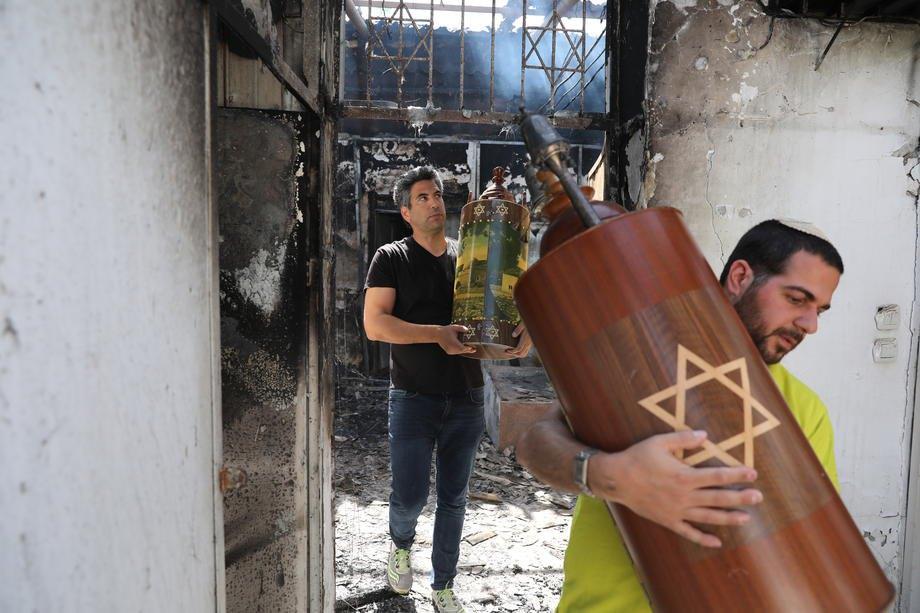 Уцілілу Тору виносять із спаленої синагоги після заворушень у Лоді, 12 травня 2021 р.