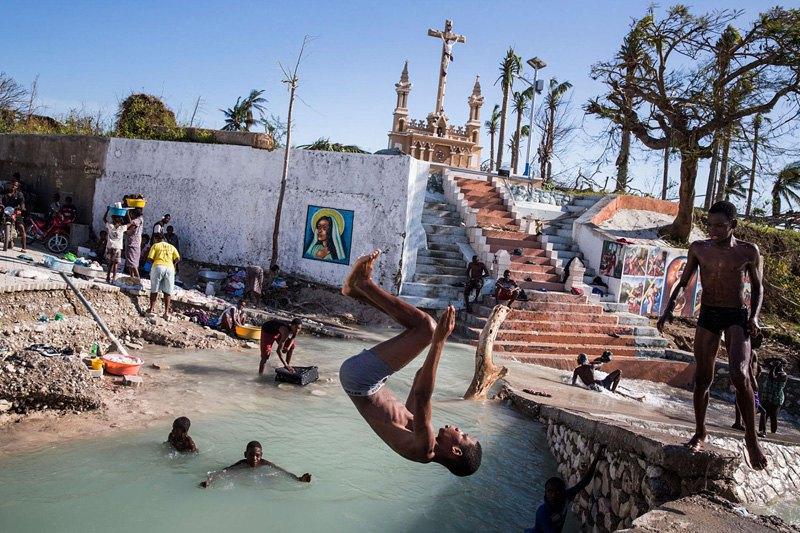 Дети купаются в реке возле разрушенного моста после урагана Мэтью в Порт Салу, Гаити.