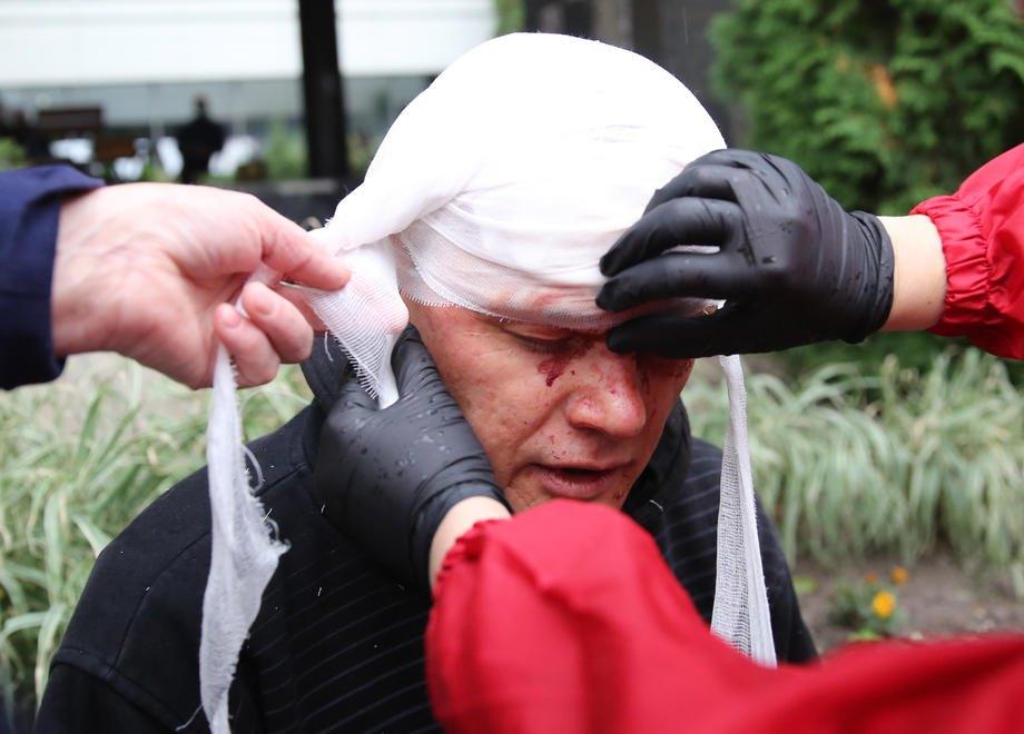 Прохожие оказывают помощь пострадавшему во время акции протеста в Минске, 10 октября