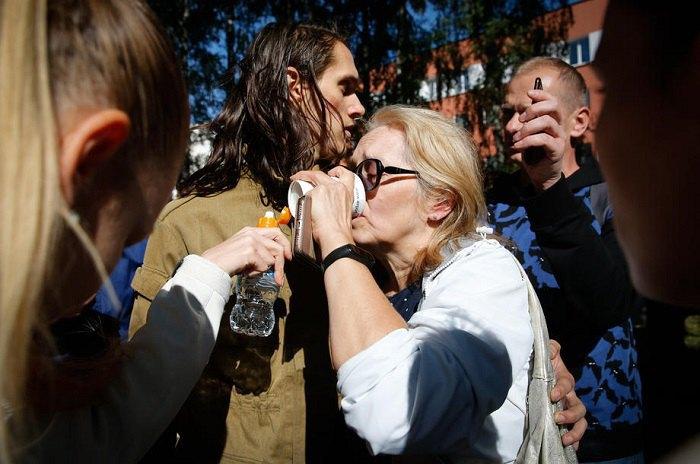 Жінка п'є воду після того, як її випустили зі слідчого ізолятора в Мінську