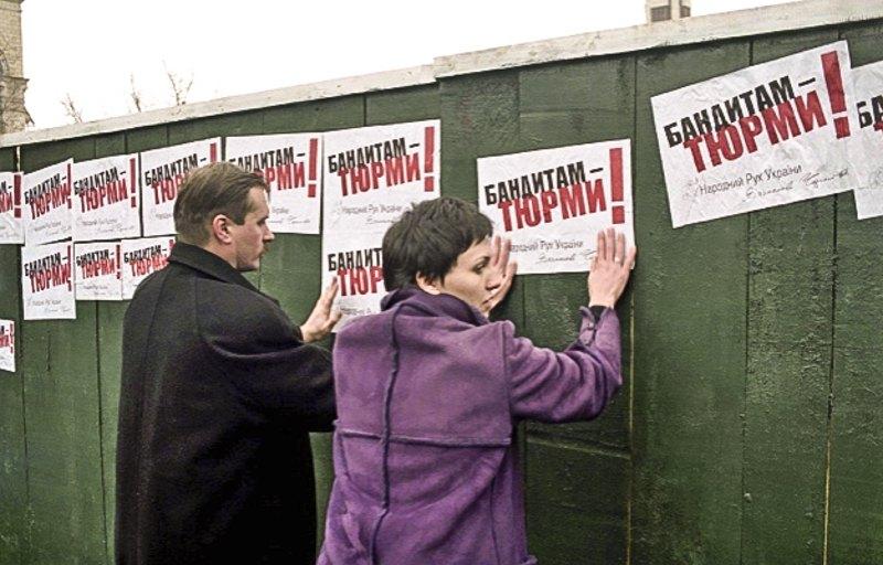 Депутат від Народного Руху України Тарас Чорновіл і дружина вбитого журналіста Мирослава Гонгадзе розклеюють листівки на Майдані Незалежності під час мітингу на Хрещатику, 6 лютого 2001 року .