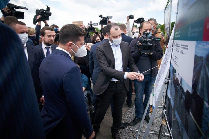 Голова «Укравтодору» Олександр Кубраков показує на стендах президенту Володимиру Зеленському, які дороги ремонтуються.