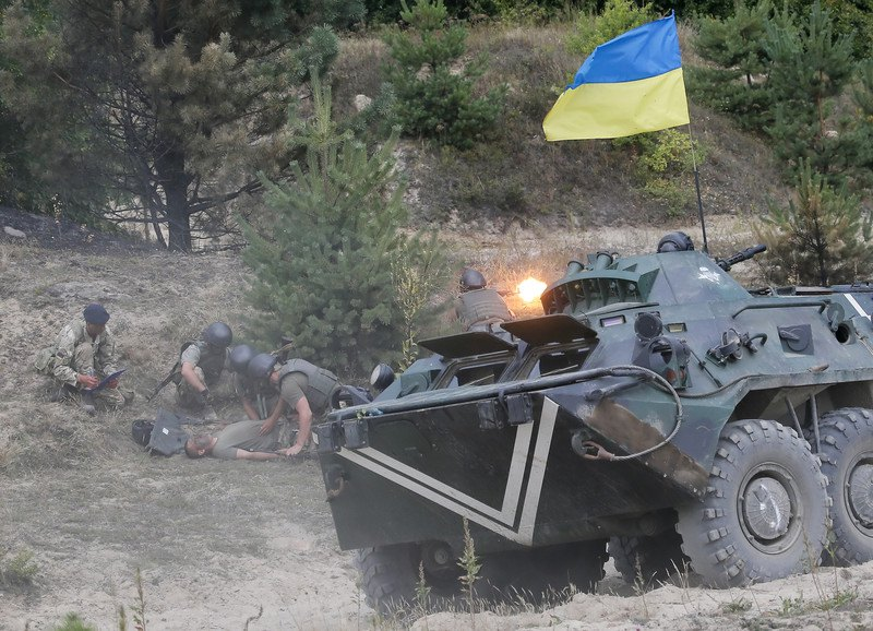 Украинские солдаты и британский инструктор (слева) во время учений на полигоне Перлявка недалеко от Житомира, 11 августа 2015.