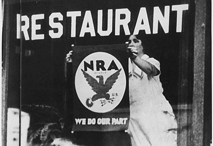 Жінка вішає у вітрині ресторану плакат на підтримку урядової програми NRA.
