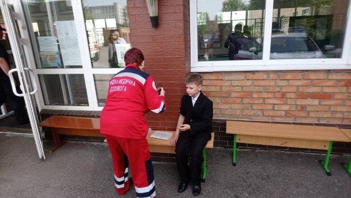 Врач скорой помощи осматривает школьника, которому стало плохо во время линейки в Черкассах
