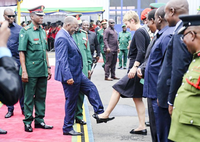 Президент Танзании Джон Магуфули (слева) приветствует гостью из делегации Германии