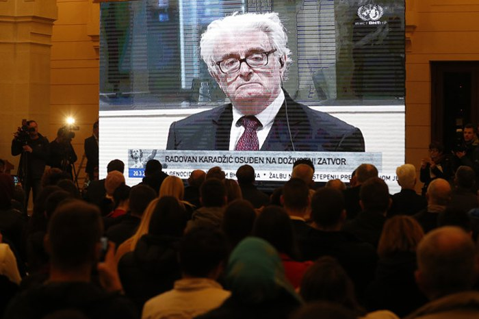 Боснийцы наблюдают за судебным заседанием Международного трибунала по бывшей Югославии, посвященного приговору лидеру боснийских сербов военного времени Радовану Караджичу, Сараево, Босния, 20 марта 2019.