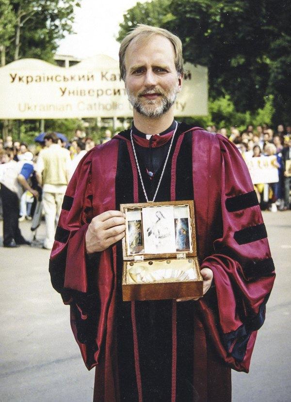 Борис Ґудзяк перед місцем майбутнього кампусу УКУ, територію якого у цей день посвятив Папа Іван Павло ІІ. В руках переносний престол з часів підпілля УГКЦ, який був вручений Папі як символічний дарунок, 26 червня 2001 року